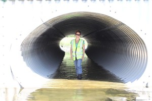 Sarah Schacher, P.E., completes a final inspection of the Valdez Tidal Flats Culvert Replacement in Valdez, Alaska. The depressed culverts, designed by Schacher and her team, accommodate the fish population in the tidal flats.