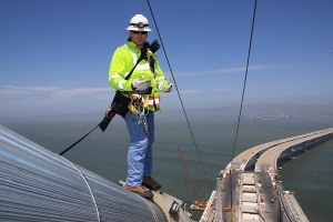 Photographer Bill Hall captured Caltrans Transportation Engineer Matt Bruce inspecting the cable band installation of the San Francisco-Oakland Bay Bridge. American Bridge Fluor completed the cable band installation Matt inspected atop the new main cable of the self-anchored suspension structure.