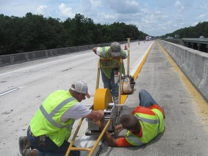 Richie Morehouse really puts his back into his work as his colleagues with Jenkins Painting, Inc., Ryan Manfready and Matt Hendricks, work to get the thermoplastic down on a Florida Department of Transportation resurfacing project on Interstate 10 in Madison County, Florida.