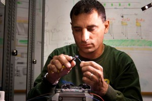 Sam Sakran, FDOT District Four maintenance contractor, carefully gathers the ends of fiber optic to be spliced together.