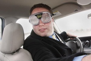 A driver wears vision impairment goggles while trying to navigate a car through an Idaho State Police closed track as part of a highway safety impaired-driving demonstration. The Idaho Transportation Department helps provide funds to purchase educational tools for law enforcement agencies to use with community outreach efforts.