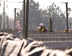 A lone worker stands amid girders during overpass construction in Boise, Idaho.