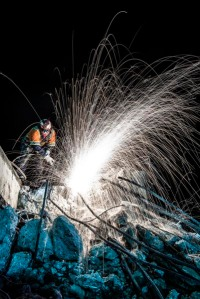 An unknown worker cuts through re-enforcing rebar in the concrete rubble of a demolished bridge on State Route Four in Antioch Ca. The bridge was demolished to make room for the widening of the Highway and the addition of a light rail system.
