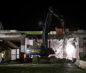 A large excavator fitted with a hydraulic hammer breaks down a section of  concrete bridge on State Route Four in Antioch Ca. The bridge was demolished to make room for the widening of the highway and the addition of a light rail system.