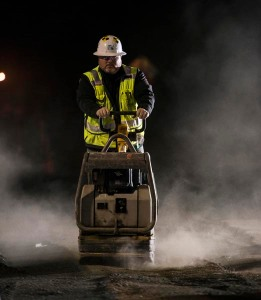 Unknown worker uses gravel compactor to slat ten gravel that was disturbed during a night time highway closure.