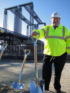 MassDOT Deputy Chief Engineer for Construction, Mike McGrath, in front of the temporary Fore River Bridge. This bridge, which crosses a major shipping channel just south of Boston, is being replaced in one of MassDOT's Mega Projects. The new bridge will improve mobility for motor vehicles and ships.
