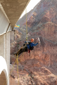 Trask Bradbury of Gemini Rope Solutions gives the thumbs-up while rapelling off the Mike O'Callaghan-Pat Tillman Memorial Bridge (Hoover Dam Bypass) during a routine biennial bridge inspection. The concrete-steel composite arch bridge looms 840 feet above the Colorado River and is the 2nd largest bridge in the United States at 1,900 feet in length.