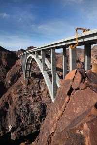 The long arm of a Nevada DOT bridge inpsection truck descends down and around the Mike O'Callaghan-Pat Tillman Memorial Bridge (Hoover Dam Bypass) delivering bridge inspectors to their work on a routine biennial bridge inspection. The concrete-steel composite arch bridge looms 840 feet above the Colorado River and is the 2nd largest bridge in the United States at 1,900 feet in length.