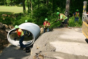 State workers install an upgraded culvert on State Route 772 in Pike County, Ohio. The old culvert was too small to accommodate the water flow, resulting in roadway flooding during heavy rains. The new culvert also prepares the road for planned resurfacing.