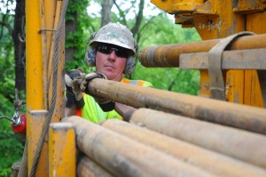 Standing above the Muskingum River on State Route 555 near Zanesville Ohio, Drilling Crew Chief Michael Lewis of the Office of Geotechnical Engineering unloads a drill rod in preparation for a soil sample on an upcoming bridge replacement project.