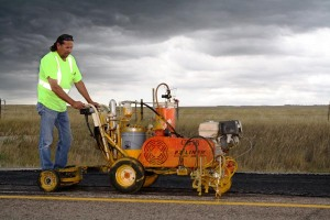 Donnie Boyd, Highway Maintenance Worker from Mission, repaints the center stripe on Highway 83 in Todd County after crews completed an asphalt patching project. Storm clouds threatened, but didn't stop these dedicated workers from getting the job done!