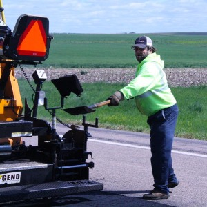 Loren Haynes, Highway Maintenance Worker from Martin shovels asphalt behind the paving machine as the crew works to repair highways in south central South Dakota. Asphalt patching is essential for not only the safety of the traveling public, but also extends the usable life of the pavement.