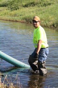 Matt Vobr, Highway Maintenance Worker from the Winner area, isn't afraid to get wet to get the job done! Matt is monitoring a pipe being used to drain a ditch to get to a plugged culvert that was causing flooding on Highway 47 in south central South Dakota.