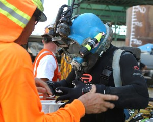 A diver prepares to perform an underwater inspection of the pilings of the Commodore Schuler F. Heim replacement Bridge. The old bridge is the last vertical-lift bridge that crosses the Cerritos Channel in the Port of Los Angeles.