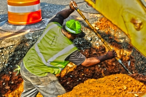 DOT maintenance worker Keith Monette spreads soil around a repaired pipe on SR 3 Connector at SR 120 in Cobb County. The damaged pipe caused a sinkhole at the entrance to a local business. The temperature on this day is near 90 degrees.