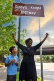 "Accompanied by her grandson Awesome, American recording artist, songwriter, businesswoman, humanitarian and author Gladys Knight, known as the ""Empress of Soul"", raises her hands in jubilation during a Georgia DOT ceremony dedicating a new highway in her name."
