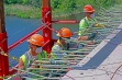 Three bridge workers drill holes for the installation of anchorages for the walk way forms on the Richard I. Bong Bridge in Duluth, Minnesota. The bridge is undergoing a two-year reconstruction project.