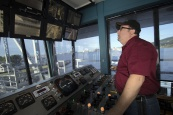 Chief Bridge Operator, David Campbell, watches several monitors as he prepares to life the Duluth Aerial Lift Bridge. Campbell must ensure that pedestrians and motorists are safely off the bridge before it is lifted. The bridge lifts approximately 4,500 times yearly to allow passage of ships and high-profile watercraft.