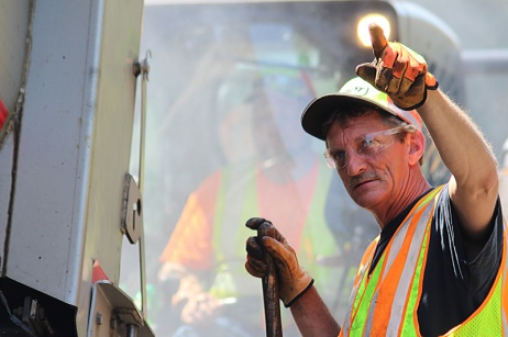 David Mattison, MnDOT transportation generalist, signals to the driver of a tandem dump truck during a mill and fill blacktop patching project on Interstate 35 near Sturgeon Lake, Minnesota. Steaming hot mix has just been dropped from the truck obscuring everything behind Mattison.