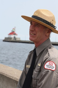 Kevin Gange, US Army Corps of Engineers park ranger, talks to a group of tourists who have gathered near the Duluth Aerial Lift Bridge/Duluth Harbor entry. Gange leads tours twice daily during the summer, sharing information about the bridge and the economic benefits and history of Great Lakes shipping.