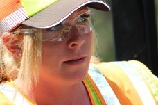 Shannon McIntyre, MnDOT transportation generalist, looks ahead as she drives a Caterpillar compactor over hot asphalt on the edge line along Interstate 35 near Sturgeon Lake, Minnesota.
