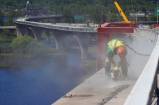 A worker on the Richard I. Bong Bridge reconstruction project creates dust clouds as he saw cuts near the edge of the bridge. At 8,320 feet, the Richard I. Bong Bridge is the longest bridge in Minnesota. The bridge serves as a link between Duluth, Minnesota and Superior, Wisconsin.