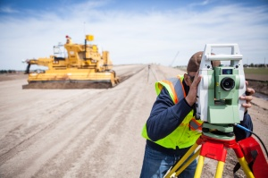 Work continues and a grader passes along the new bypass near Kearney, Nebraska, as a worker surveys the grade.