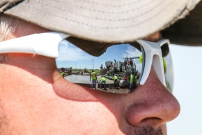 Work of pouring concrete is framed in the reflection of a supervisor's sunglasses on the new Kearney bypass along Interstate 80 in Nebraska.