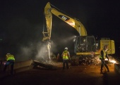 It's all in a night's work as a construction crew moves quickly to deconstruct an old bridge over I-235 in Oklahoma City during an overnight closure.