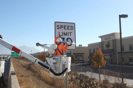 Workers apply a new 70 mph sticker to a sign on Interstate 15 in Lindon, Utah. In an effort to optimize mobility and decrease speed differentials, UDOT increased the urban speed limit to 70 on Dec. 10, 2014. 99 signs along the Wasatch Front were changed out that day.