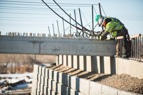 Construction of Wildlife Crossing on US Highway 85 just south of the Missouri River. Contractor places concrete beams across abutments with large crane.