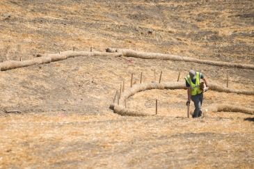 Environmental protection measures such as fiber rolls being installed on a construction project to convert a section of the US 83 Northwest ByPass just north of US 2 from 2 lanes to 4.