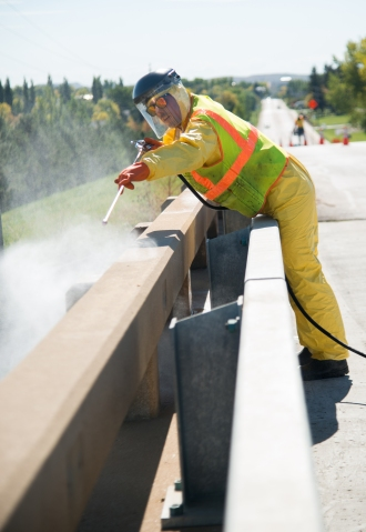 Digital Smart Cone deployed in a maintenance workzone with technology to assist in worker safety. Tyler Strand applies a new silane solution to an Interstate bridge to help with preventative maintenance by helping shed water and preventing corrosion.